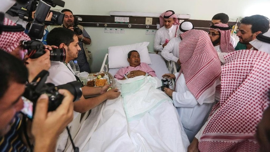 Abdul Rahman Al Sudais, Imam of the Grand Mosque in Mecca, talks to one of the victims of Friday's crane accident at the mosque while visiting Al-Noor specialist hospital in Mecca, Saudi Arabia, Sunday, Sept. 13, 2015. High winds were to blame for the toppling of a massive crane that smashed into the mosque and killed over 100 people ahead of the start of the annual hajj pilgrimage, the head of Saudi Arabia's civil defense directorate said Saturday. (AP Photo/Mosa'ab Elshamy)