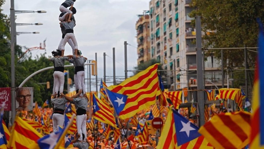 Members of a Castellers complete their human tower as others wave pro-independence Catalan flags, known as the Estelada flag, during a rally calling for the independence of Catalonia, in Barcelona, Spain, Friday, Sept. 11, 2015. Advocates of independence for Spain's northeastern region of Catalonia on Friday launched their campaign to try to elect a majority of secessionists in regional parliamentary elections on Sept. 27. (AP Photo/Francisco Seco)