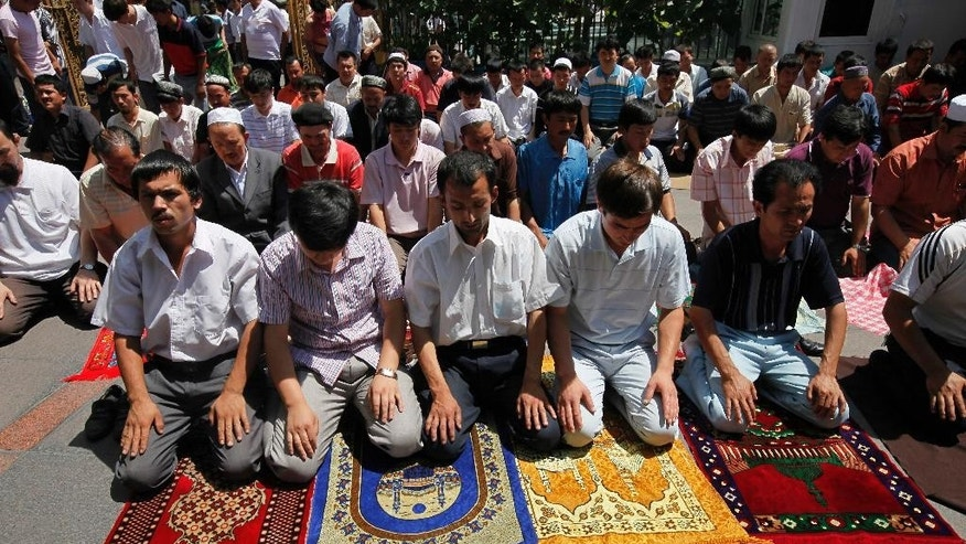 FILE - In this July 10, 2009, file photo, Uighur men pray on their own in a mosque despite city wide closure of the mosques, in Urumqi, western China's Xinjiang province. Arrests made and details revealed about the Aug. 17, 2015, Bangkok bombing that killed 20 people have raised the question of whether members of an ethnic and religious minority from China's far west were involved. (AP Photo/Eugene Hoshiko, File)