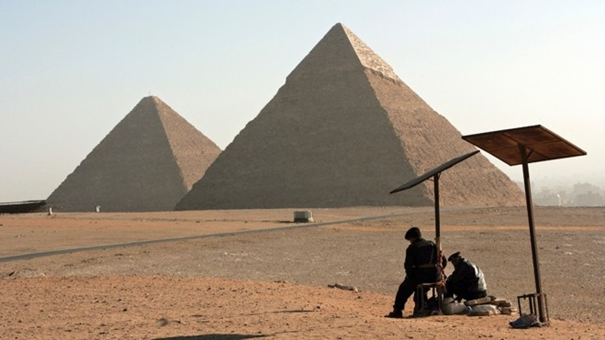 CAIRO, EGYPT - FEBRUARY 9. Two Egyptian Tourist Police Officers guard the area of the Great Pyramides Chephren and Mycerinus seen on the background on February 9, 2006 in Giza, Cairo, Egypt. (Photo by Marco Di Lauro/Getty Images)