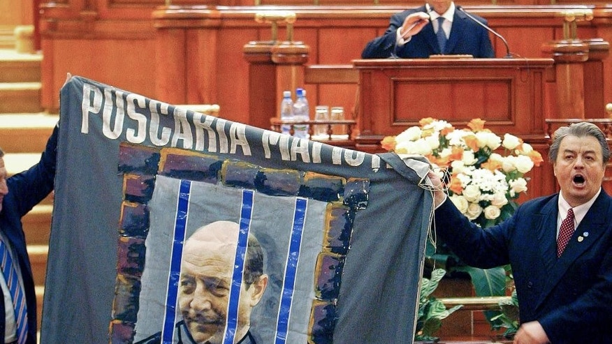FILE -  In this Monday, Dec. 18, 2006 file picture, Romanian President Traian Basescu, top, adjust his microphone as ultranationalist leader Corneliu Vadim Tudor, right, carries a banner depicting Basescu behind bars, and shouts attempting to interrupt the President's speech during a special Parliament session in Bucharest Romania. Tudor, aged 65,  died Monday, Sept. 14, 2015 in a hospital in the Romanian capital following a cardiac arrest.(AP Photo/Vadim Ghirda, File)