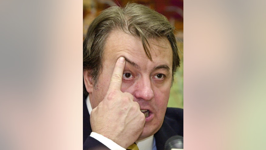 FILE - In this Sunday Nov. 26, 2000 file picture, Romanian ultranationalist politician Corneliu Vadim Tudor touches his forehead during a press conference in Bucharest, Romania. Tudor, aged 65, died Monday, Sept. 14, 2015 in a hospital in the Romanian capital following a cardiac arrest.(AP Photo/Vadim Ghirda, File)