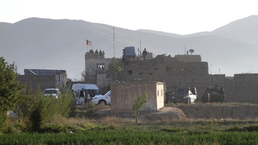 Afghan security members stand guard on the roof of the main prison building after an attack in Ghazni province, eastern Afghanistan, Monday, Sept. 14, 2015. An Afghan official says that more than 350 inmates have escaped after an attack by the Taliban insurgents on the main prison. (AP Photo/Rahmatullah Nikzad)