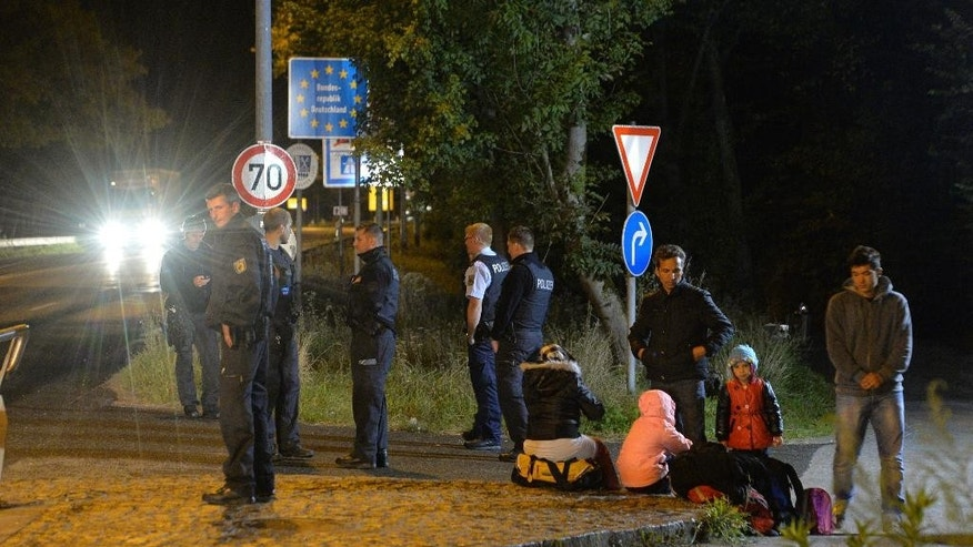 German federal police stand beside refugees waiting at the German-Austrian border between Freilassing, Germany, and Salzburg, Austria, Monday, Sept. 14, 2015. Germany introduced temporary border controls Sunday to stem the tide of thousands of refugees streaming across its frontier, sending a clear message to its European partners that it needs more help with an influx that is straining its ability to cope.  (AP Photo/Kerstin Joensson)