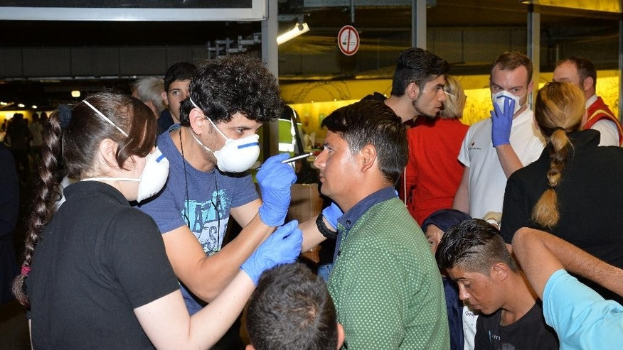 "A refugee receives medical treatment in a parking garage in the main rail station in Salzburg Austria, Sunday, Sept. 13, 2015. At least four countries Friday firmly rejected a European Union plan to impose refugee quotas to ease a worsening migrant crisis that Germany's foreign minister said was ""probably the biggest challenge"" in the history of the 28-nation bloc. (AP Photo/Kerstin Joensson)"