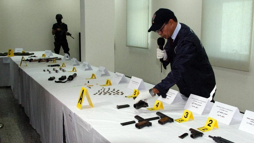 An official with the Central Bureau of Judicial Investigation gestures toward confiscated weapons with a commando in the background on MOnday Sept. 14, 2015 in Sale, Morocco. Morocco's counter-terrorism unit has announced the dismantling of a militant cell based in the southern city of Essaouira that was in contact with the Islamic State group (AP Photo/Paul Schemm).