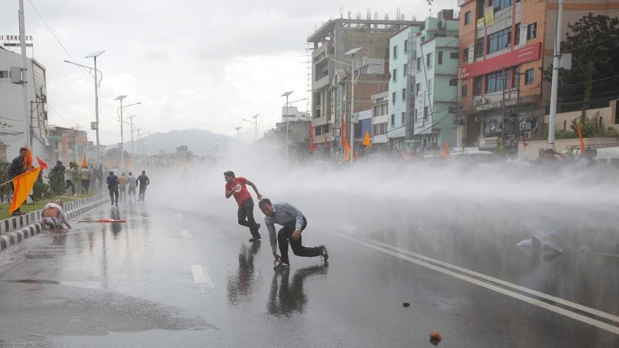 Nepalese police use water cannon to disperse Hindu protestors after they tried to enter a restricted area near the Constituent Assembly hall in Kathmandu, Nepal, Monday, Sept 14, 2015. Nepal's Constituent Assembly rejected calls to revert the Himalayan nation back to a Hindu state during voting on a draft of the long-delayed new constitution.(AP Photo/Bikram Rai)