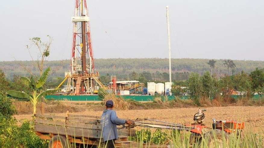 In this May 24, 2015, image provided by Chainarong Sretthachau, a villager works in a field next to a gas drilling rig operated by American company APICO and its subsidiary Tatex Thailand in Na Mun, Kalasin province, Thailand. More than 200 residents in communities near well sites have complained to Thailand's National Human Rights Commission about skin and respiratory problems and some have been hospitalized, according to commission member Dr. Nirun Pitakwatchara. (Chainarong Sretthachau via AP)