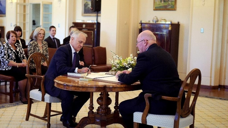 Malcolm Turnbull, center, is sworn in by Australia's Governor-General Sir Peter Cosgrove, right, as prime minister at Government House in Canberra, Tuesday, Sept. 15, 2015. Turnbull was sworn in Australia's 29th prime minister after a surprise ballot of his conservative Liberal Party colleagues voted 54-44 on Monday night to replace Prime Minister Tony Abbott only two years after he was elected. (Lukas Coch/Pool Photo via AP)
