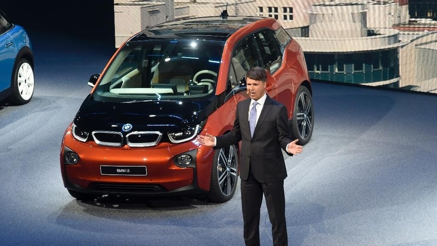 BMW CEO Harald Krueger stands in front of a BMW i3 electric vehicle on the first press day of the Frankfurt Auto Show IAA in Frankfurt, Germany, Tuesday, Sept. 15, 2015. The car show runs through Sept. 27. (AP Photo/Jens Meyer)