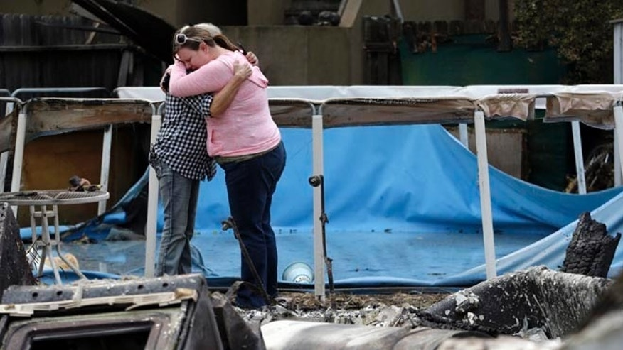 Deanna Hingst, right, embraces her mother Shirley Leuzinger as they stand at the family's destroyed home Monday, Sept. 14, 2015, in Middletown, Calif. Two of California's fastest-burning wildfires in decades overtook several Northern California towns, killing at least one person and destroying hundreds of homes and businesses and sending thousands of residents fleeing highways lined with buildings, guardrails and cars still in flames. (AP Photo/Elaine Thompson)