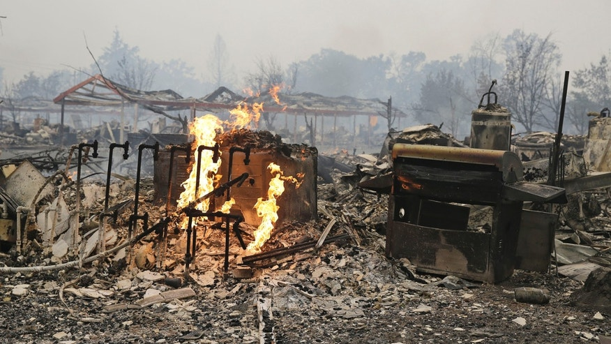 Flames continue to burn near gas lines at a destroyed apartment complex Sunday, Sept. 13, 2015, in Middletown , Calif. California Gov. Jerry Brown has declared a state of emergency in Lake and Napa Counties after a wildfire charred more than 60 square miles within 12 hours, prompting thousands to flee their homes. Brown said Sunday the declaration will expedite debris removal and waive fees to people who need to replace official documents lost in the fire.  The blaze, about 100 miles north of San Francisco, has destroyed an unconfirmed number of homes and other buildings and damaged highways and other infrastructure.(AP Photo/Eric Risberg)