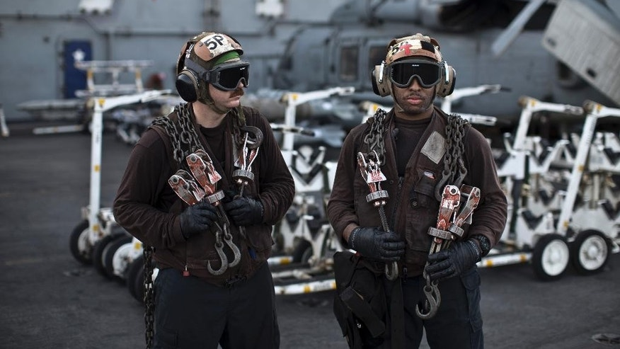 In this Thursday, Sept. 10, 2015 photo, U.S. Navy air wing plane captains carry chains as they pause on the flight deck of the USS Theodore Roosevelt aircraft carrier. Plane captains are identified by wearing brown shirts and are responsible for preparing the aircraft for flight. Every day, the steam-powered catapult aboard this massive aircraft carrier flings American fighter jets into the sky, on missions to target the extremist Islamic State group in Iraq and Syria.(AP Photo/Marko Drobnjakovic)