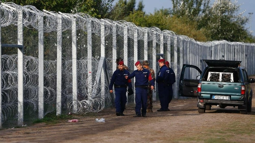 Hungarian police officers check a hole at the fence where migrants tried to cross the border line between Serbia and Hungary in Roszke, southern Hungary, Tuesday, Sept. 15, 2015. Hungary is set to introduce much harsher border controls at midnight — laws that would send smugglers to prison and deport migrants who cut under Hungary's new razor-wire border fence. The country's leader was emphatically clear that they were designed to keep the migrants out. (AP Photo/Matthias Schrader)