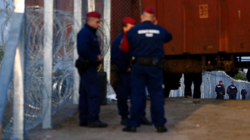 Hungarian police officers control the border line beside a rail wagon prepared with barbwire at the border line between Serbia and Hungary in Roszke, southern Hungary, Tuesday, Sept. 15, 2015. Thousands of people walked this route to Austria and Germany. Hungary are set to introduce much harsher border controls at midnight — laws that would send smugglers to prison and deport migrants who cut under Hungary's new razor-wire border fence. The country's leader was emphatically clear that they were designed to keep the migrants out. (AP Photo/Matthias Schrader)