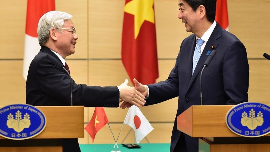 Vietnamese Communist Party General Secretary Nguyen Phu Trong, left, shakes hands with Japan's Prime Minister Shinzo Abe, right, following their joint press announcement at Abe's official residence in Tokyo Tuesday, Sept. 15, 2015. Trong is on a four-day official visit to Japan. (Kazuhiro Nogi/Pool Photo via AP)