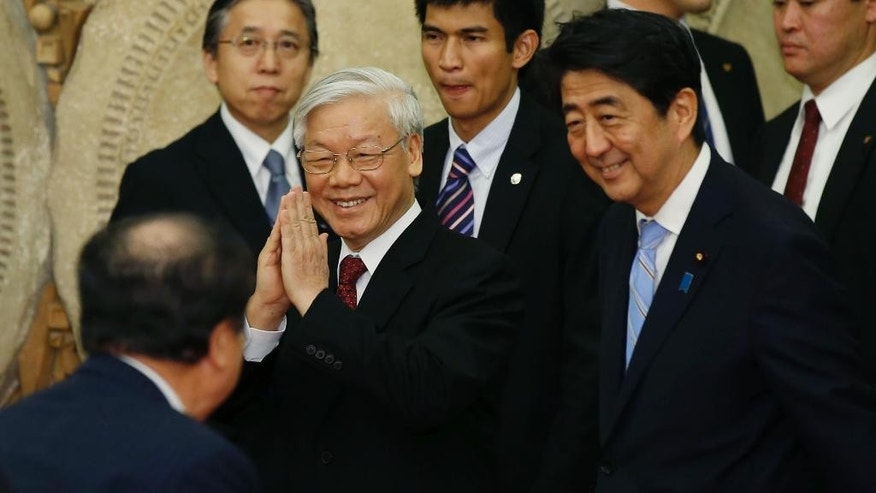 Vietnam's Communist Party General Secretary Nguyen Phu Trong, left, escorted by Japan's Prime Minister Shinzo Abe, right, greets a guest as they arrive at a welcome dinner hosted by Abe at Abe's official residence in Tokyo Tuesday, Sept. 15, 2015. (Toru Hanai/Pool Photo via AP)
