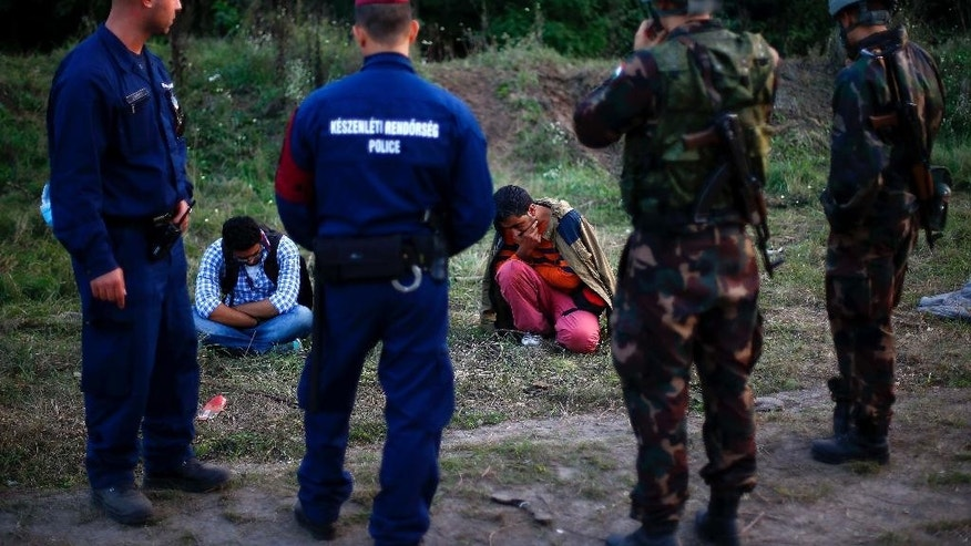Migrants sit on the ground arrested by Hungarian police officers and soldiers after they tried to cross the border line between Serbia and Hungary in Roszke, southern Hungary, Tuesday, Sept. 15, 2015. Hungary deployed a boxcar bristling with razor wire to close a key border crossing and warned of a new era of swift deportations Monday as governments across Europe debated how to share the burden of housing hundreds of thousands seeking refuge — and whether the continent's hard-won policy of passport-free travel could survive the unrelenting flow of humanity. (AP Photo/Matthias Schrader)