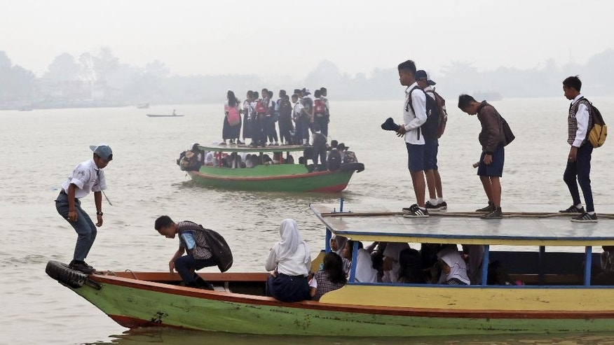 Students ride on boats to go to school as haze from wildfires blanketed the Ogan River in Palembang, South Sumatra, Indonesia, Tuesday, Sept. 15, 2015. Wildfires caused by illegal land clearing in Indonesia's Sumatra and Borneo islands often spread choking haze to neighboring countries such as Malaysia and Singapore. (AP Photo)