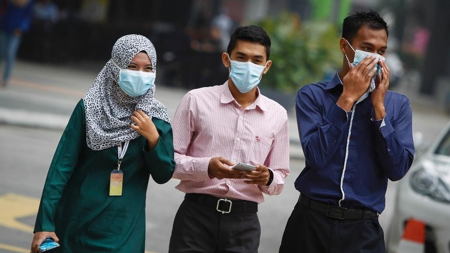 Malaysians wear masks due to the haze in Kuala Lumpur, Malaysia on Tuesday, Sept. 15, 2015. A layer of heavy haze has forced Malaysian authorities to shut schools in four states, including Kuala Lumpur, with officials to begin cloud seeding operations to try to induce rain to help clear the air. (AP Photo/Joshua Paul)