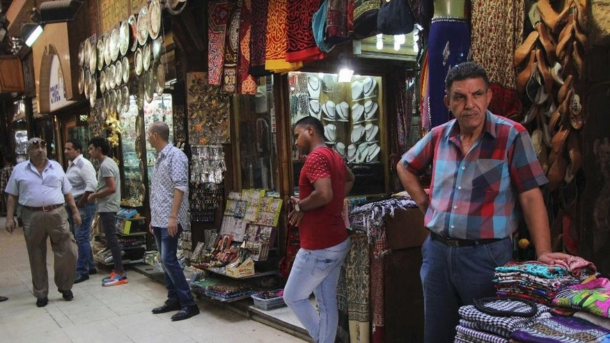 Store clerks wait for customers outside their businesses at Cairo's Khan el-Khalili bazaar in Egypt, Tuesday, Sept. 15, 2015. Sunday's airborne attack by Egyptian forces on tourists in the western desert, among the deadliest involving tourists in Egypt, came as the country has been trying to revive its vital tourism industry since the turmoil following the 2011 uprising that toppled President Hosni Mubarak. (AP Photo/Mohammed Abu Zaid)
