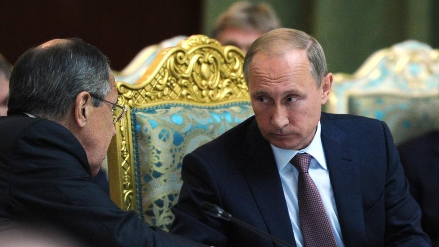 Russian President Vladimir Putin listens to Russia's Foreign Minister Sergey Lavrov, left, at the meeting of the Collective Security Treaty Organization (CSTO) in Dushanbe, Tajikistan, Tuesday, Sept. 15, 2015. Russian President Vladimir Putin on Tuesday strongly defended Moscow's military assistance to the Syrian government, saying it's impossible to defeat the Islamic State group without cooperating with the Syrian government. (Mikhail Klimentyev/RIA-Novosti, Kremlin Pool Photo via AP)
