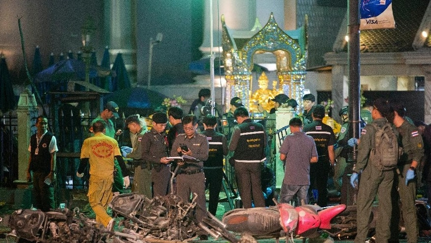 FILE - In this Aug. 17, 2015 file photo, police investigate the scene at the Erawan Shrine after an explosion in Bangkok. Thailand's national police chief said Tuesday, Sept. 15 that authorities are now certain that last month's deadly bombing at the shrine was related to the trafficking of Uighur Muslims from China to Turkey. (AP Photo/Mark Baker, File)