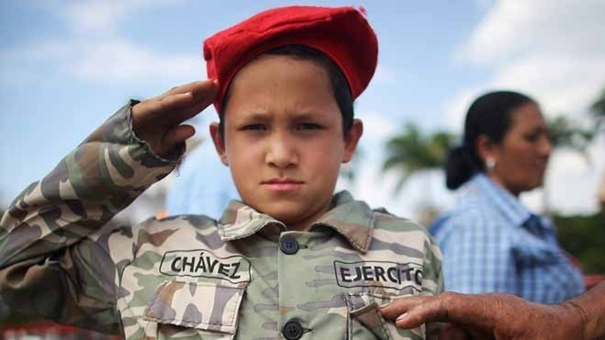 A boy poses in a Chavez uniform outside the Military Academy on March 9, 2013 in Caracas, Venezuela.