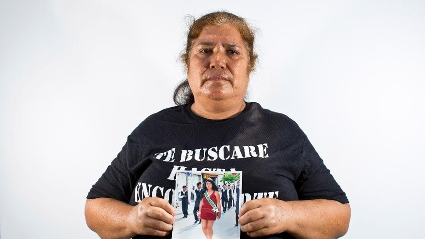 In this May 26, 2015 photo, Rosa Segura Giral holds up a photo of her daughter, Berenice Navarijo Segura, in Iguala, Mexico. On the morning of her high school graduation, 19-year-old Berenice left for a beauty salon appointment, less than a five-minute drive from home, and vanished into the ranks of Mexico's missing. Segura Giral says she has not lost hope for her daughter. (AP Photo/Dario Lopez-Mills)
