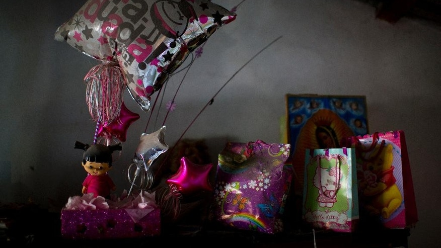 In this June 1, 2015, 2015 photo, high school graduation gifts for Berenice Navarijo Segura gather dust, awaiting her return atop a cabinet in her mother's home in Cocula, Mexico. On Berenice's graduation day, July 1, 2013, seventeen people, including Berenice, disappeared from Cocula, more than a year before 43 students from a teachers college were detained by police in nearby Iguala and never seen again. (AP Photo/Dario Lopez-Mills)