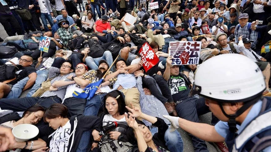 Protesters lie down arm in arm together as a police officer tries to clear them in front of the venue hotel for a public hearing on the security legislation in Yokohama, south of Tokyo, Wednesday, Sept. 16, 2015. Opposition lawmakers and thousands of demonstrators were making last-ditch protests in a political showdown Wednesday as Japan's ruling party started a final push to pass security legislation to expand the role of the country's military. (Yohei Fukai/Kyodo News via AP) JAPAN OUT, MANDATORY CREDIT