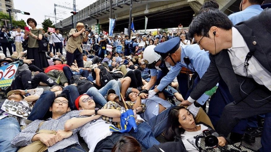 Protesters lie down arm in arm together as police officers try to clear them in front of the venue hotel for a public hearing on the security legislation in Yokohama, south of Tokyo, Wednesday, Sept. 16, 2015. Opposition lawmakers and thousands of demonstrators were making last-ditch protests in a political showdown Wednesday as Japan's ruling party started a final push to pass security legislation to expand the role of the country's military. (Kyodo News via AP) JAPAN OUT, MANDATORY CREDIT