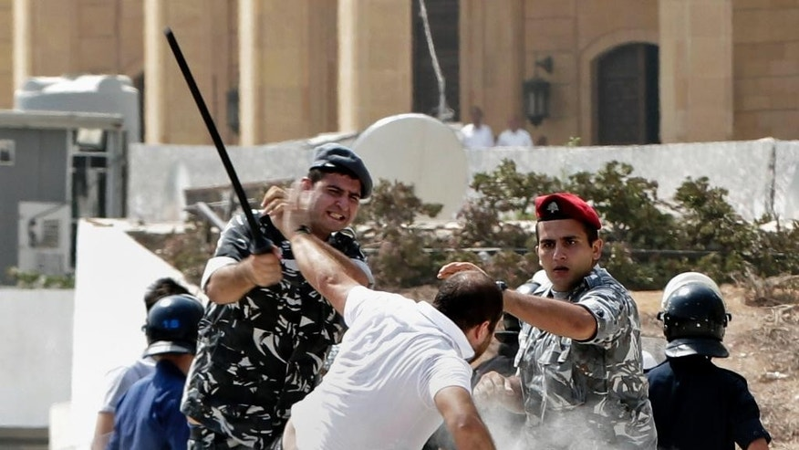 Lebanese riot policemen strike an anti-government protester during clashes on a road leading to the parliament building, in downtown Beirut, Lebanon, Wednesday, Sept. 16, 2015. Lebanese police beat back protesters in downtown Beirut Wednesday ahead of the second session of dialogue between senior politicians, amid widespread anger over the government's failure to deal with the country's trash crisis and other political problems. (AP Photo/Bilal Hussein)
