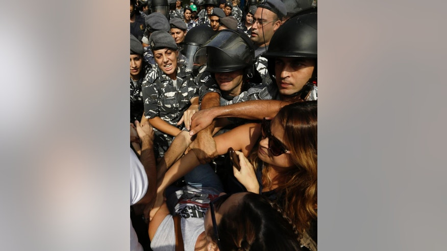 Lebanese anti-government protesters clash with policewomen on a road leading to the parliament building before a scheduled meeting of political leaders to try to solve the on-going trash crisis and government dysfunction, in downtown Beirut, Lebanon, Wednesday, Sept. 16, 2015. (AP Photo/Hassan Ammar)