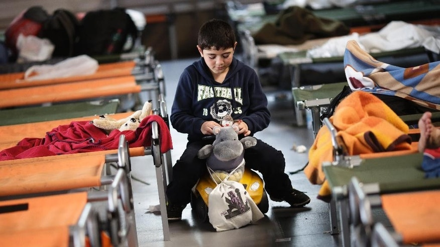 A boy sits on a toy car and plays with stuffed animals as he waits with other refugees for registration at the temporary registration center of the southern German border town Passau, Tuesday, Sept. 15, 2015. The refugees were brought to the center from trains, cars or were picked up on streets.  (AP Photo/Markus Schreiber)