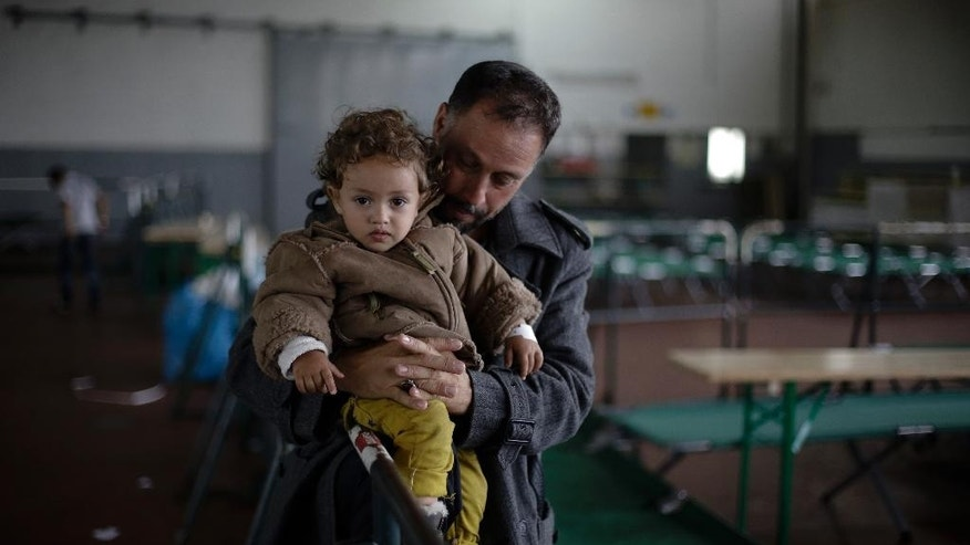 A man from Afghanistan holds his child as they wait for registration at the temporary registration center of the southern German border town Passau, Tuesday, Sept. 15, 2015. The refugees were brought to the center from trains, cars or were picked up on streets.  (AP Photo/Markus Schreiber)