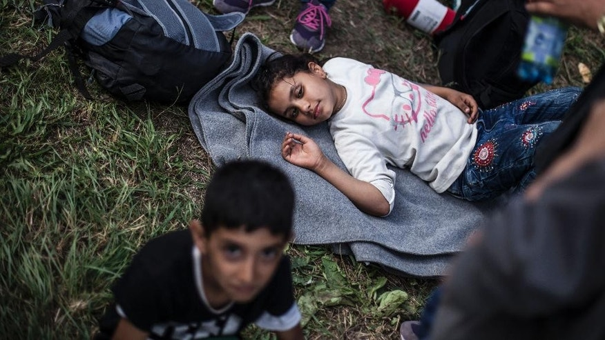 A Syrian child rests after arriving at the train station in Hegyeshalom, Hungary, near the border with Austria on Tuesday Sept. 15, 2015. Austria's Interior Ministry says temporary border controls with Hungary will be in effect immediately after midnight Tuesday. The ministry says the measure could be extended to the country's borders with Slovenia, Italy and Slovakia, if needed. That reflects the possibility that migrants now streaming into Austria from Hungary could instead try to cross into Austria over those borders in large numbers. (AP Photo/Manu Brabo)