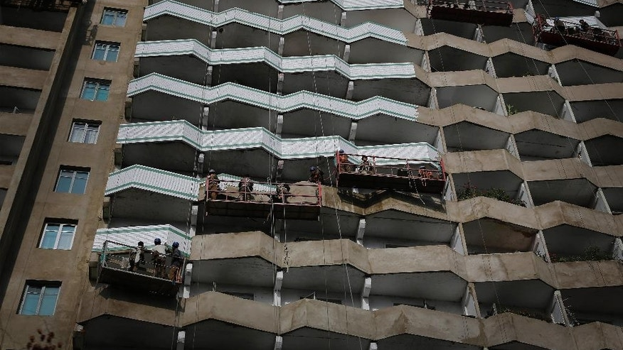In this Tuesday, Sept. 15, 2015, photo, workers paint a building in Pyongyang, North Korea. North Korea is already in high gear as it prepares to mark the 70th anniversary of the founding of its ruling party. Shock brigades of soldier-builders are toiling around the clock to paint bridges, build stages and finish high-rise apartments. North Korea's capital now even has bicycle lanes. (AP Photo/Wong Maye-E)