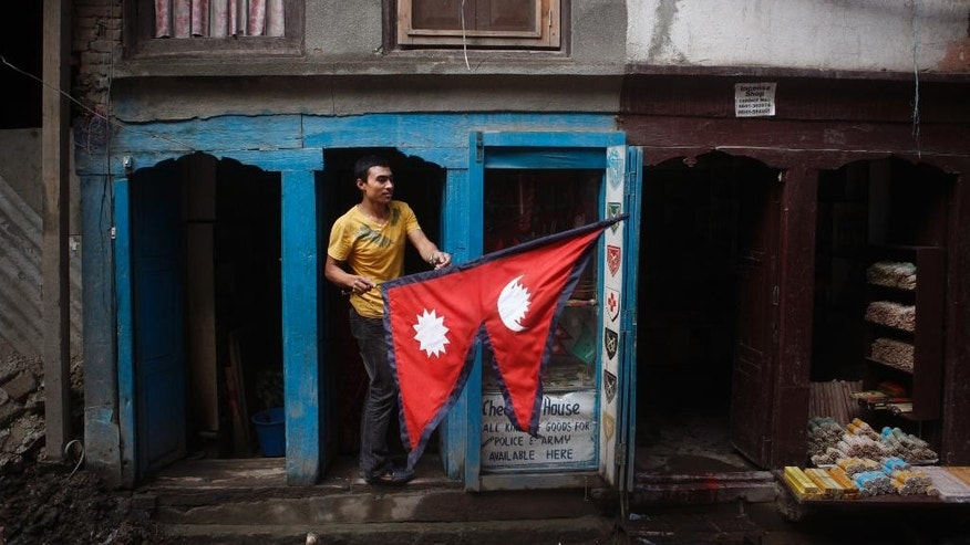 A man carries a Nepalese flag as he stands outside his stall in Kathmandu, Nepal, Wednesday, Sept. 16, 2015. Nepal has been roiled by weeks of protests by Hindus and some ethnic groups who object to the draft constitution, which is expected to be passed Thursday after 10 years of tense efforts since Nepal's centuries-old monarchy was abolished. While pro-democracy demonstrators in 2006 wanted the country be made a secular republic, some now demand it be restored as a Hindu nation. (AP Photo/Niranjan Shrestha)