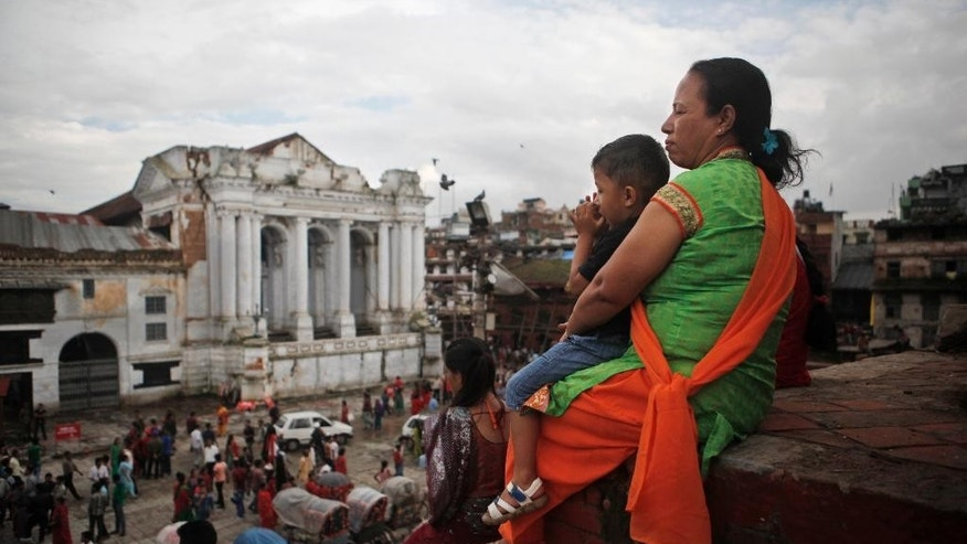 A Nepalese woman sits with a child at the Basantapur Durbar Square in Kathmandu, Nepal, Wednesday, Sept. 16, 2015. Nepal has been roiled by weeks of protests by Hindus and some ethnic groups who object to the draft constitution, which is expected to be passed Thursday after 10 years of tense efforts since Nepal's centuries-old monarchy was abolished. While pro-democracy demonstrators in 2006 wanted the country be made a secular republic, some now demand it be restored as a Hindu nation. (AP Photo/Niranjan Shrestha)