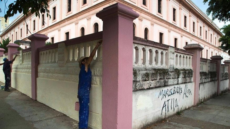 Workers apply a fresh coat of paint to the walls surrounding the archdiocese residence, in preparation for the visit of Pope Francis, in Havana, Cuba, Tuesday, Sept. 15, 2015. Francis will visit Cuba from Sept. 19-22, before arriving in the United States, making him the third pontiff to visit the island nation. (AP Photo/Desmond Boylan)