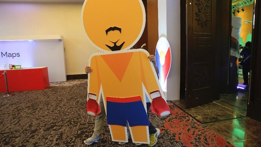 """Men carry a """"Pegman"""" version of Filipino boxing icon Manny Pacquiao with his distinctive mustache and beard in suburban Pasay, south of Manila, Philippines, Wednesday, Sept. 16, 2015. Pacquiao and tourism officials say images of the Philippine capital and the country's main tourist spots on Google's Street View could help attract more visitors to the country. (AP Photo/Aaron Favila)"""