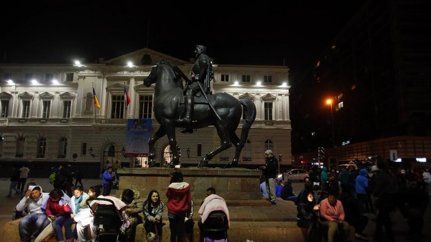 Residents sit next to an equestrian statue, in Santiago's main square after a 8.3 earthquake, in Santiago, Chile, Wednesday, Sept. 16, 2015. The powerful earthquake hit Chile's northern coast causing buildings to sway in Santiago and other cities and sending people running into the streets. (AP Photo/Luis Hidalgo)