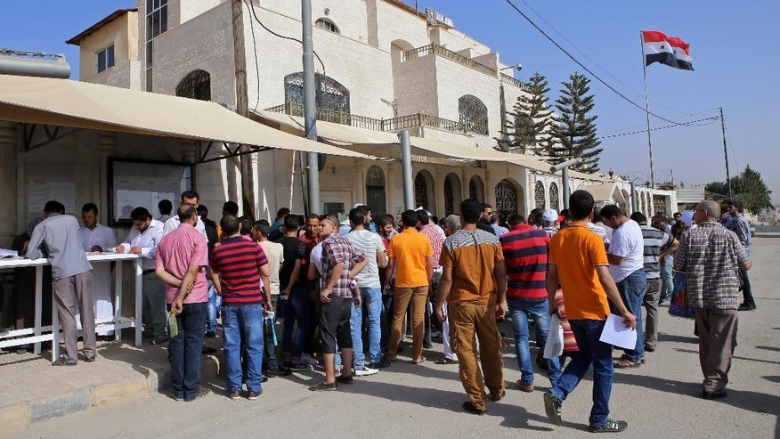 In this Tuesday, Sept. 15, 2015 photo, Syrian refugees gather outside their embassy waiting to apply for passports or to renew their old ones, in Amman, Jordan. Hundreds of Syrian refugees line up at their country's embassy every day for a long shot at a better future in Europe: They apply for Syrian passports that can get them into Turkey without visas, and from there plan to start dangerous journeys by sea and land to the continent. (AP Photo/Raad Adayleh)