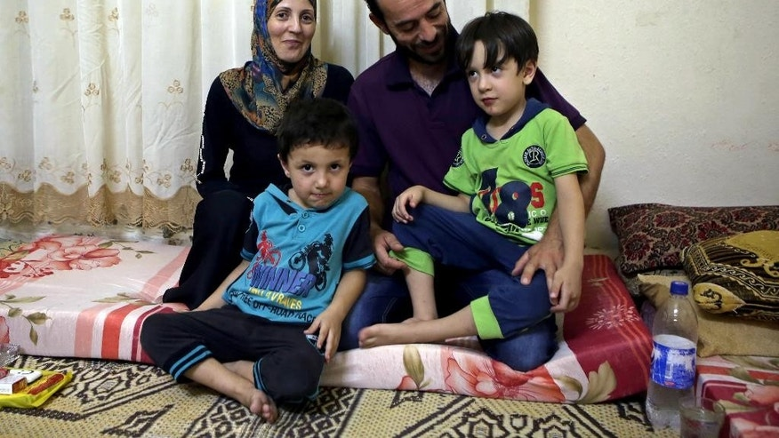 In this Sunday, Sept. 13, 2015 photo, Ali Mohammed, 33, Ali's wife Myasser Mohammed, their children, 4-year-old Omar, left, and 5-year-old Hussein, right, pose for a photo during an interview with The Associated Press, at their home in Zarqa, near Amman, Jordan. Hundreds of Syrian refugees, including the Mohammed family, line up at their country's embassy every day for a long shot at a better future in Europe: They apply for Syrian passports that can get them into Turkey without visas, and from there plan to start dangerous journeys by sea and land to the continent. (AP Photo/Raad Adayleh)