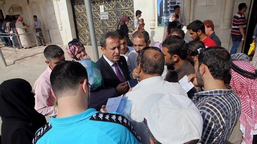 In this Tuesday, Sept. 15, 2015 photo, Syrian refugees speak to the top Syrian diplomat in Jordan, Ayman Alloush, center, as they gather outside their embassy waiting to apply for passports or to renew their old ones, in Amman, Jordan. Hundreds of Syrian refugees line up at their country's embassy every day for a long shot at a better future in Europe: They apply for Syrian passports that can get them into Turkey without visas, and from there plan to start dangerous journeys by sea and land to the continent. (AP Photo/Raad Adayleh)