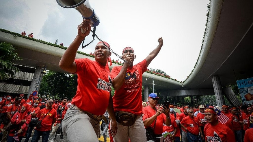 Pro-government 'red shirt' protestors shout slogans during a pro-government demonstration in Kuala Lumpur, Malaysia on Wednesday, Sept. 16, 2015. Thousands of ethnic Malays in red shirts staged a rally Wednesday to uphold Malay dominance and support Malaysian Prime Minister Najib Razak's government, following calls for Najib to step down over a $700 million financial scandal. (AP Photo/Osman Hassan)