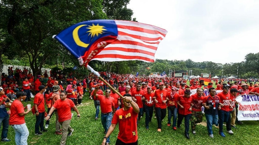 A pro-government 'red shirt' protestor waves the national flag during a rally in Kuala Lumpur, Malaysia on Wednesday, Sept. 16, 2015. Thousands of ethnic Malays in red shirts staged a rally Wednesday to uphold Malay dominance and support Malaysian Prime Minister Najib Razak's government, following calls for Najib to step down over a $700 million financial scandal. (AP Photo/Osman Hassan)