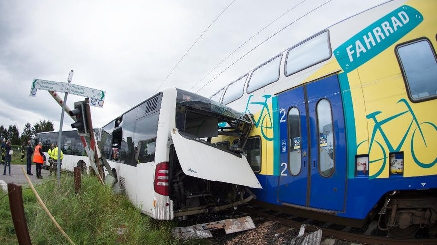 The wreckage of a school bus and a train stand on a railway crossing near Buxtehude, northern Germany, Wednesday, Sept. 16, 2015. The Train has hit the bus that got stuck on the railway crossing shortly after the bus driver had evacuated around 60 children from the vehicle. (Daniel Reinhardt/dpa via AP)