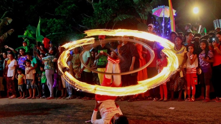 In this June 1, 2015 photo, a Sri Lankan traditional fireball dancer performs during a Buddhist temple procession in Walpola, on the outskirts of Colombo, Sri Lanka. Fireball performers primarily had the task of lighting up streets by holding torches but later turned from light-givers to performers, their torches being re-crafted and their movements choreographed to produce an epic and unforgettable spectacle. They are now an essential part of all major Sri Lanka pageants specially the famous procession of the tooth relic of the Buddha in which the relic is encased in a glittering casket atop the Royal Elephant and taken around the city of Kandy in central Sri Lanka. (AP Photo/Eranga Jayawardena)